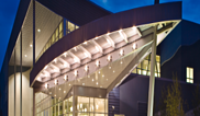 outside of building at night with lit canopy lights